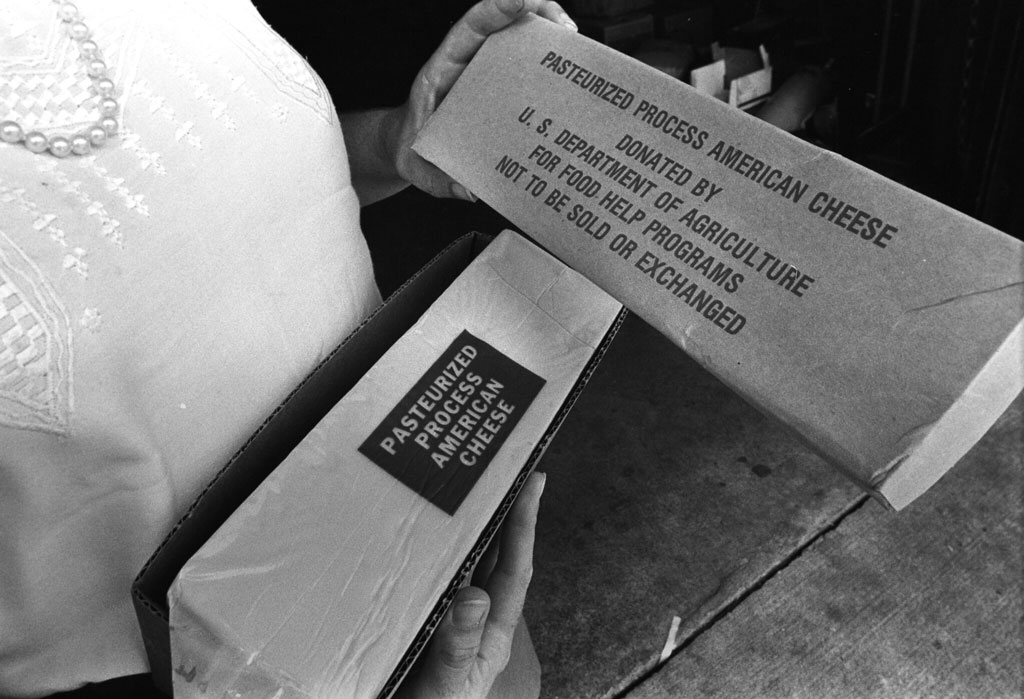 A woman holding an open box of USDA pasturized and processed American Cheese circa 1983.
