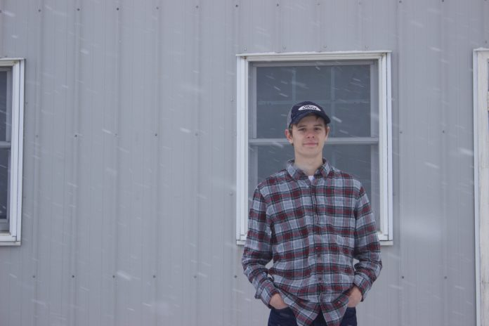 Michael Baer, 18, stands in front of a barn at Rogers Community Auction while it snows.