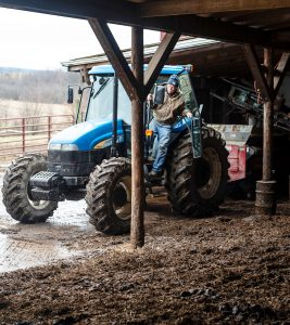 Ralph Frye jumps off his tractor after spreading manure on his farm, Pleasant Lane Farms, in Latrobe, PA.