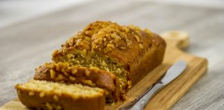 Gluten-free banana bread loaf on a cutting block with a knife and two slices cut from the end.