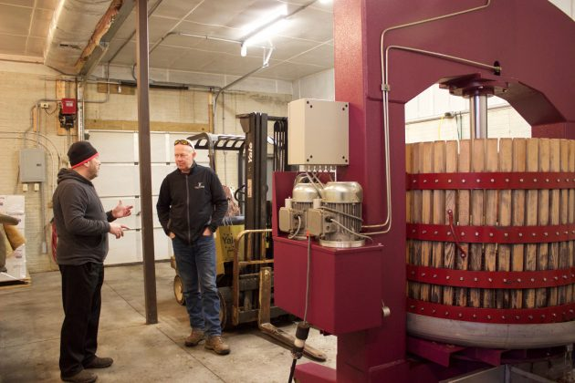 Winemaker Michael Harris and vineyard manager Gene Sigel stand in a garage near basket presses that are pressing grapes for ice wine.