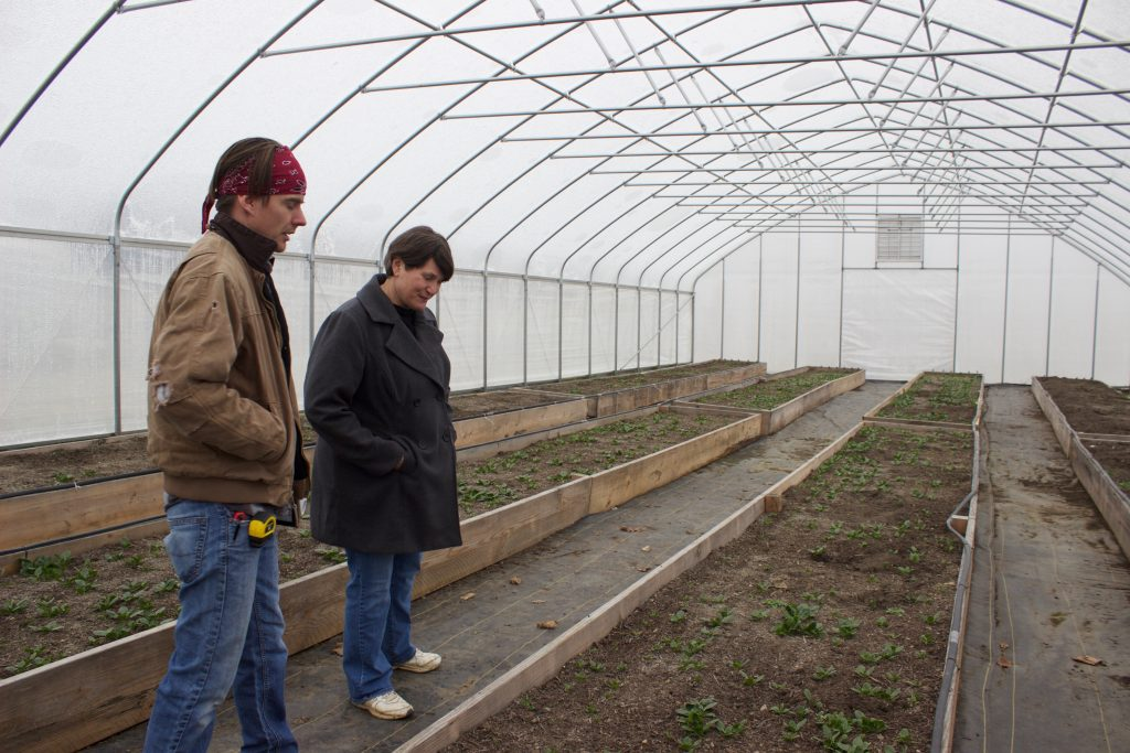 A man and a woman stand next to a raised growing bed in a high tunnel.