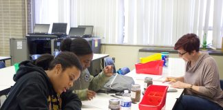 Two students and a teacher work on a soil experiment.