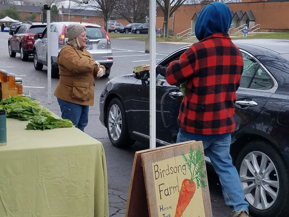 Two vendors work together to handle money and sell products at a farmers market.