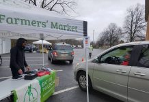 A man stands under a tent at a farmers market and talks to a woman in her car.