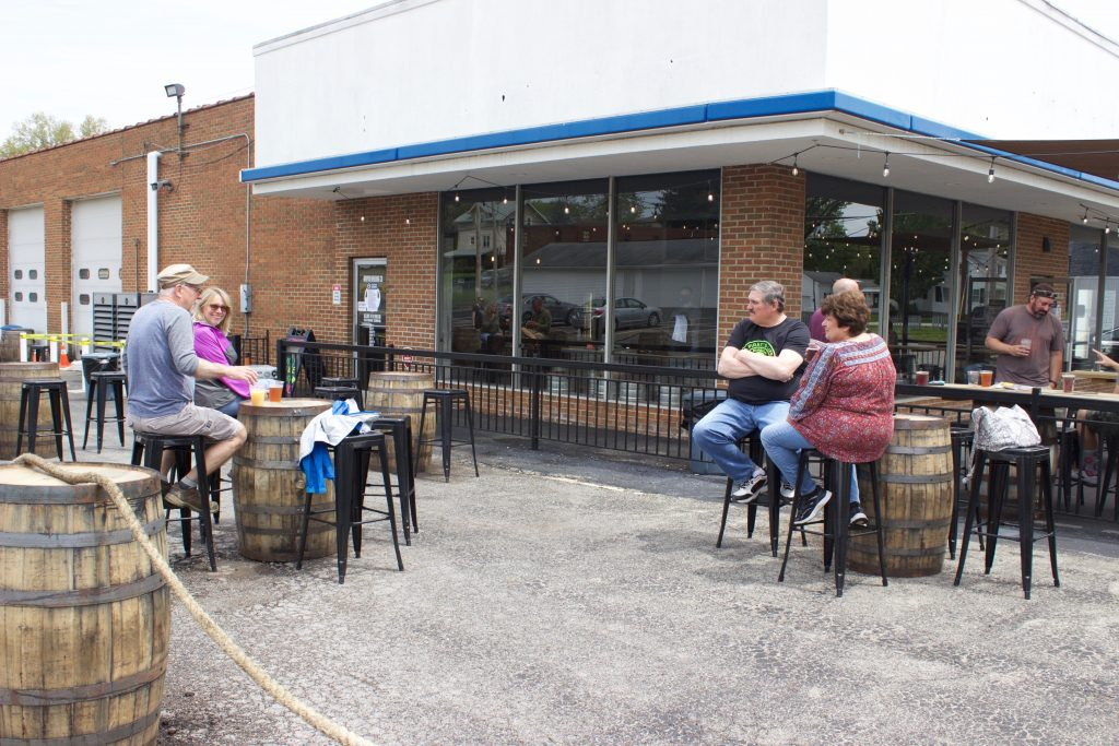 Two couples talk to each other from separated outside tables.