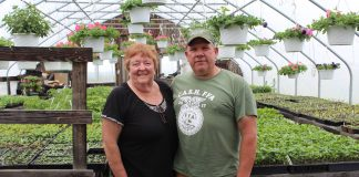 cathy and ken metrick stand in greenhouse