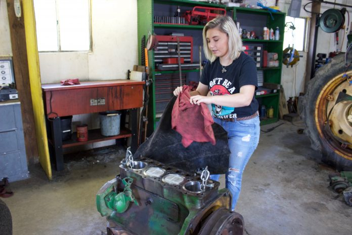 A woman pulls a cover off of a tractor engine.