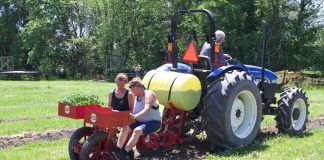 Two women sit in a vegetable planter while a man drives the tractor attached to it.