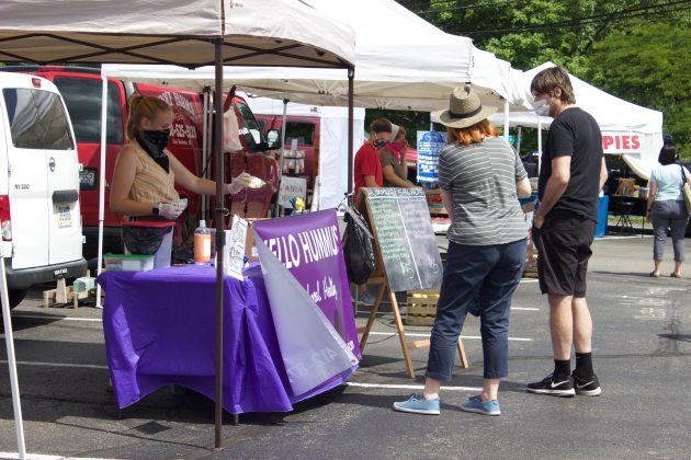 A woman serves customers from behind a stand at a farmers market.