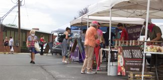 Customers walk around stands at a farmers market.