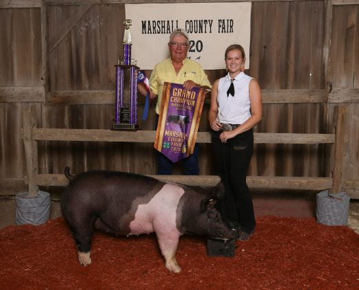 Two people stand with a hog.
