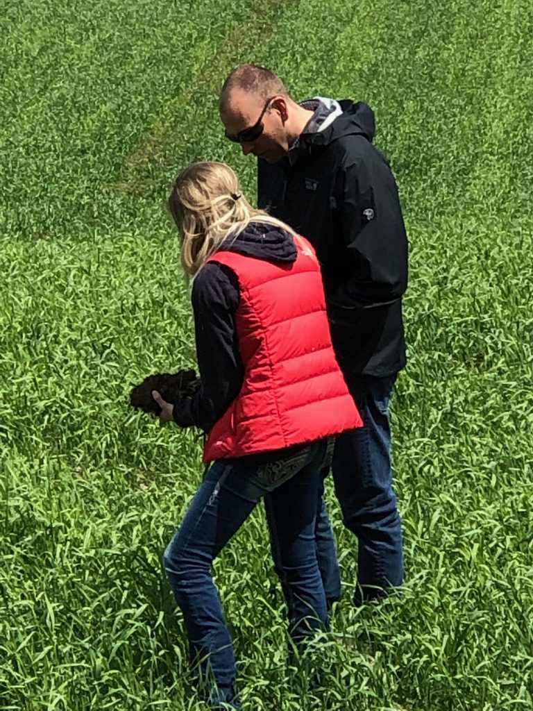 Two people stand in a field.