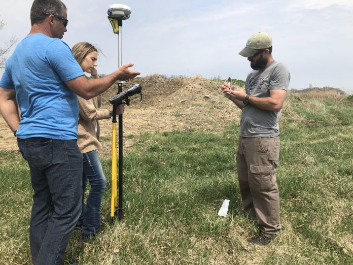 Three people stand in a field with GPS surveying equipment.
