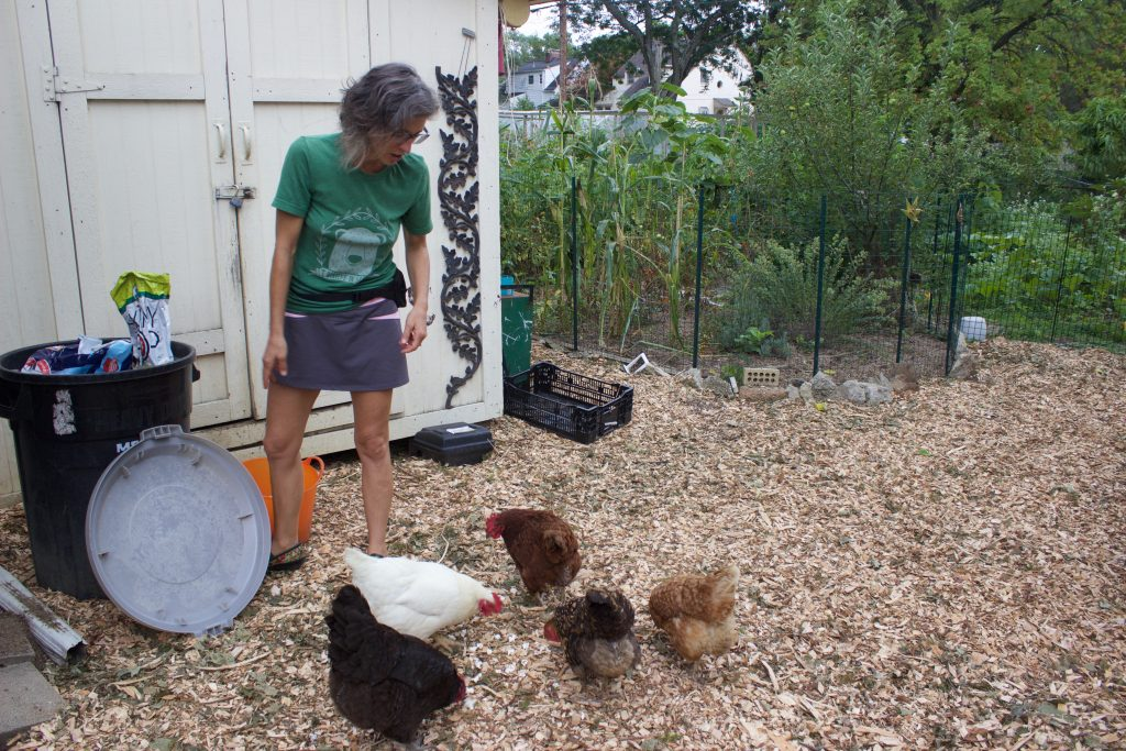 A woman feeds chickens in her backyard.