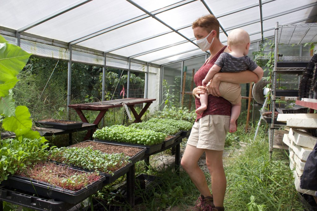 A woman stands in a greenhouse holding a baby.