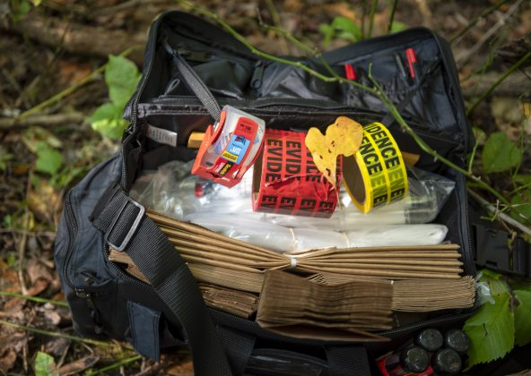 A bag filled with crime scene tape sits on the ground in the woods.