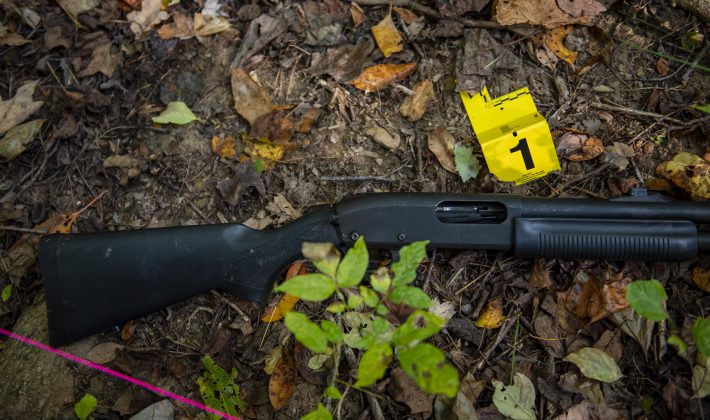 A shotgun lies on the ground with an evidence tag next to it.
