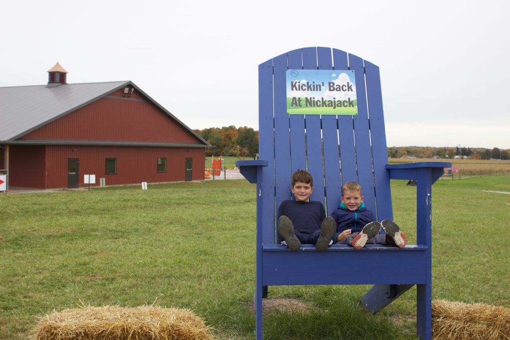 Two boys sit in an oversized chair in front of a barn.