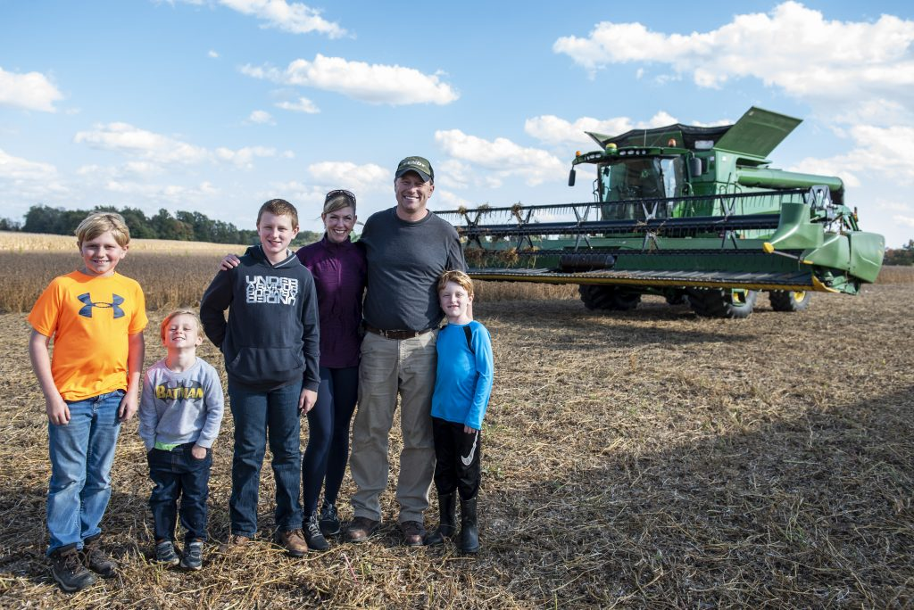 Four boys and their mother and father stand in front of a John Deere combine in a soybean field.