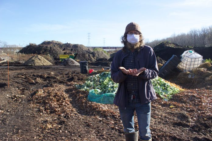 A man stands in front of a composting facility.