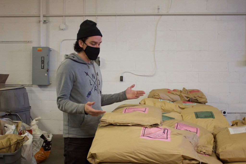 A man wearing a mask stands next to a stack of bags of soil in a warehouse.