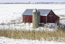 A barn and silo in the winter, with snow on the ground.