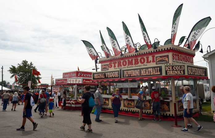 People walk around in front of concession stands at the Canfield Fair.
