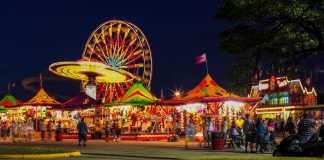 amusement rides and games with lights at a fair at night.