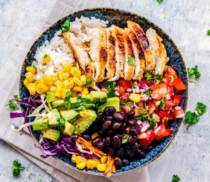 A bowl of food with rice, vegetables and protein.