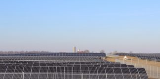solar panels sit in a field with a barn and silo in the background