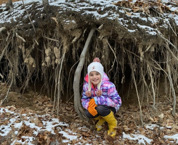 Vayda squatting in front of tree roots, holding soil together along a creek bed