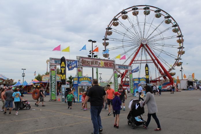 People and amusement rides at a fair.