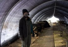 A woman stands in a tunnel under a shade cloth.