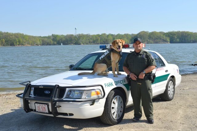 An ODNR officer and K-9 stand in front of a car.
