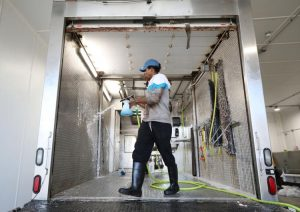 workers clean out mobile slaughter unit