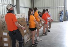 volunteers hold boxes of food