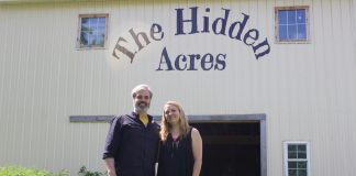 """A man and a woman stand in front of a barn with the words """"The Hidden Acres"""" painted on it."""