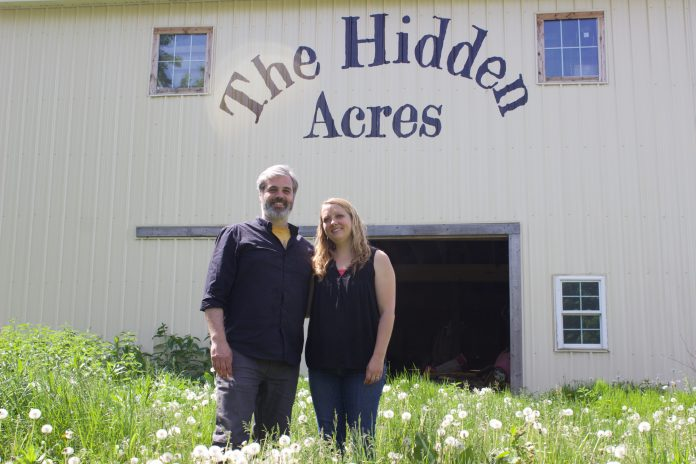 A man and a woman stand in front of a barn with the words