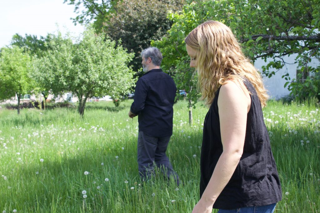 A man and woman stand in a field with tall grass and apple trees.