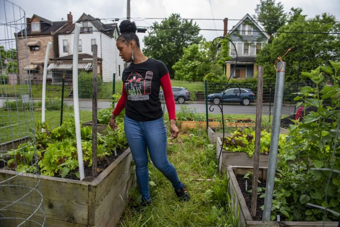 A woman stands in a garden at a community farm, in Pittsburgh.