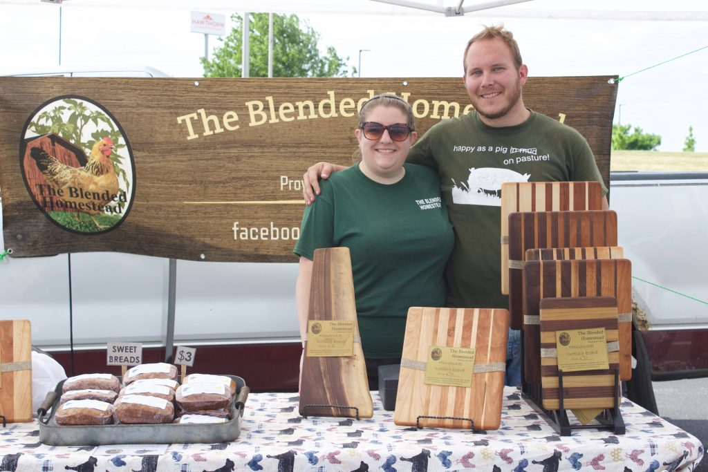 Two farmers stand behind their table at a farmers market.