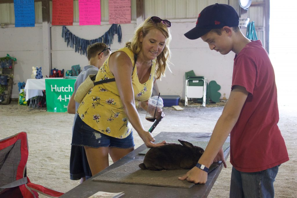 A woman pets a rabbit on a table at the fair while the rabbit's owner, a boy, looks on.