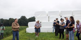 A farmer addresses a group of visitors at a farm tour.