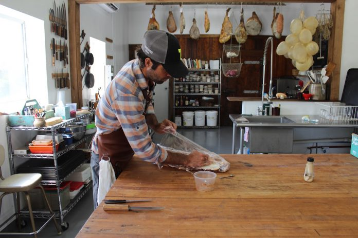 guy wrapping up meat on a table