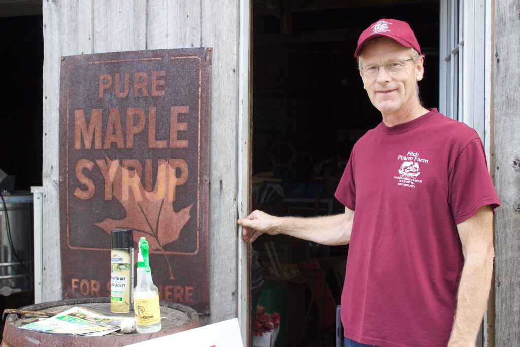 """A man stands next to a sugar house and a sign that says """"maple syrup."""""""