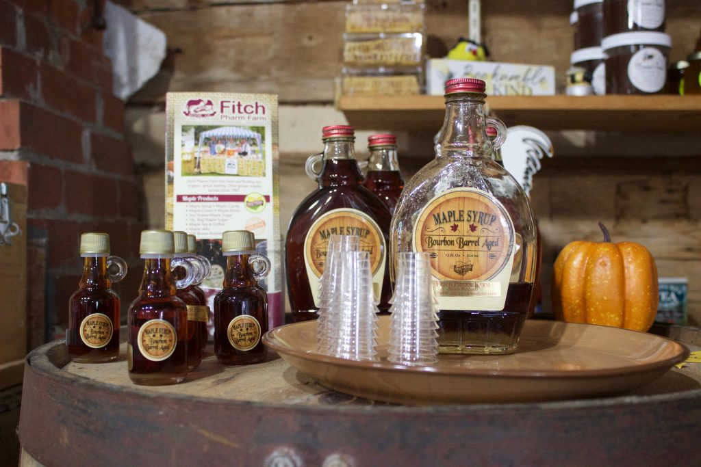 Bottles of maple syrup and small glasses set up for sampling on a table in a store.
