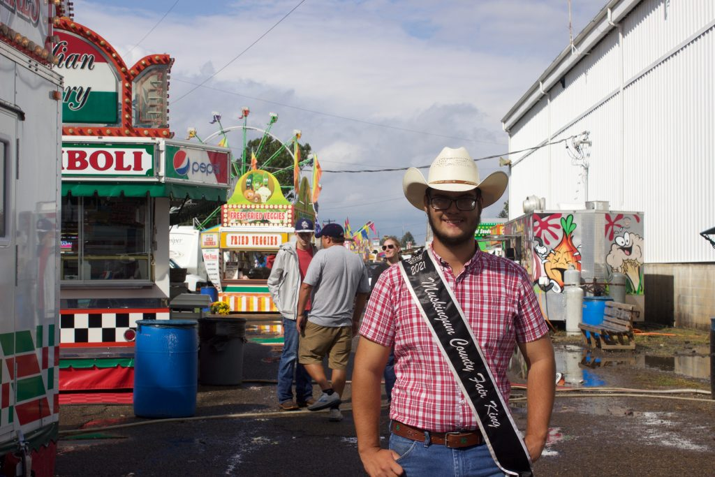 A 4-H'er with a cowboy hat and fair king sash stands on the midway at a fair.