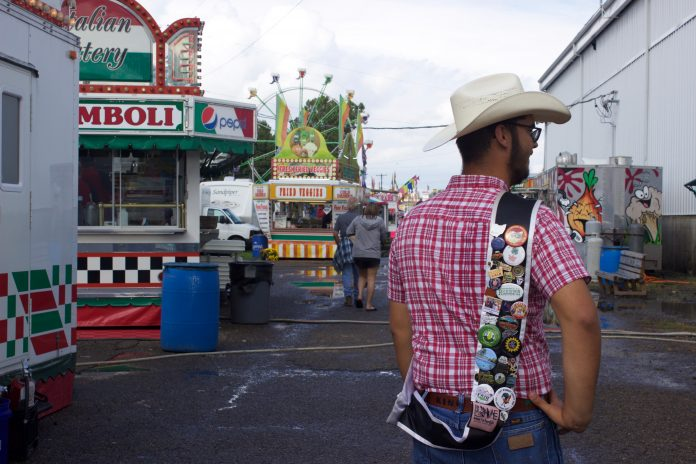 A 4-H'er shows off pins on his fair king sash on the midway at a fair.